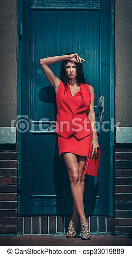 brunette woman in red dress - csp33019889