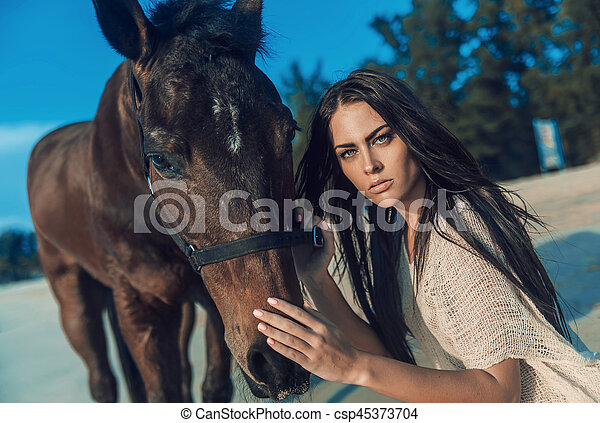 Brunette young woman posing with a stallion - csp45373704