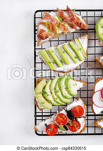 Bruschetta assortment with cream cheese, vegetables, mushrooms and bacon on the lattice - csp84330615