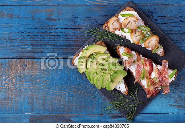 Bruschetta assortment with cream cheese, avocado, mushrooms and bacon - csp84330765