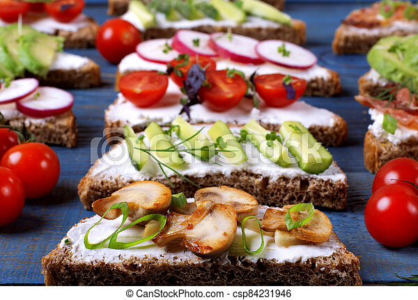 Bruschetta assortment with cream cheese, vegetables, mushrooms and bacon served on the blue wooden table - csp84231946