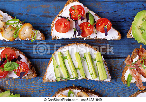 Bruschetta assortment with cream cheese, vegetables, mushrooms and bacon served on the blue wooden table - csp84231949