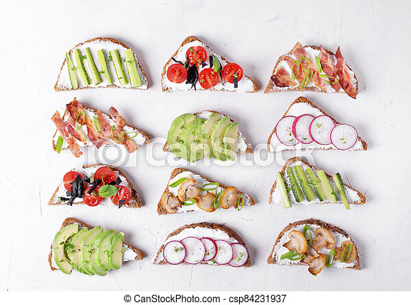Bruschetta assortment with cream cheese, vegetables, mushrooms and bacon on the white table - csp84231937