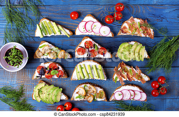 Bruschetta assortment with cream cheese, vegetables, mushrooms and bacon served on the blue wooden table - csp84231939