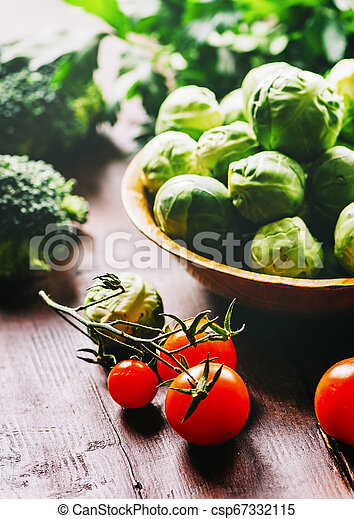 Brussel sprout, cherry tomato, broccoli, parsley and greens on rustic wooden table. - csp67332115