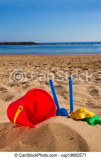 bucket with plastic beach toys in sand on sea shore - csp19662571