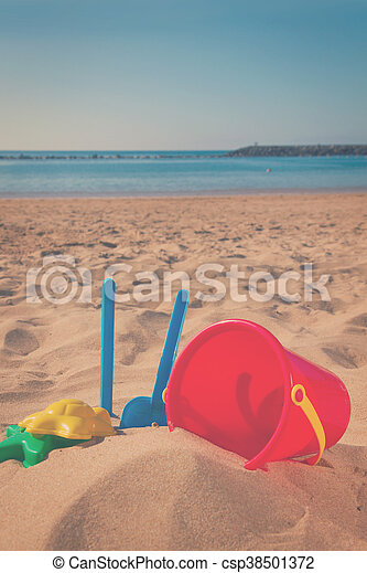 bucket with plastic beach toys in sand - csp38501372