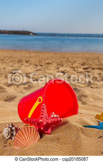 bucket with plastic beach toys in sand - csp20185087