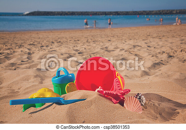 bucket with plastic beach toys in sand - csp38501353