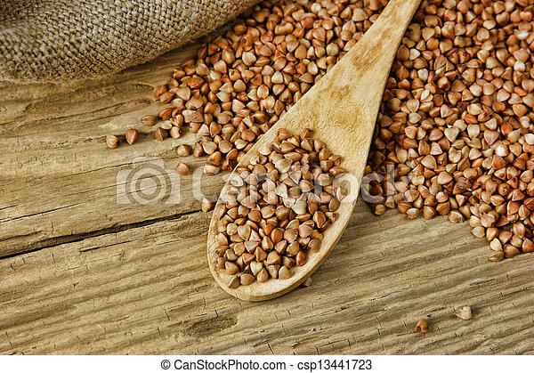 buckwheat groats and wooden spoon - csp13441723
