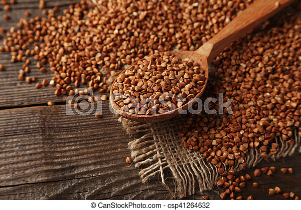Buckwheat in a spoon on brown wooden background - csp41264632
