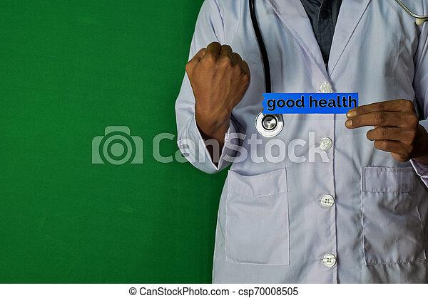 Un médico de pie, sostiene el texto de papel de buena salud sobre el fondo verde. Un concepto médico y de salud. - csp70008505