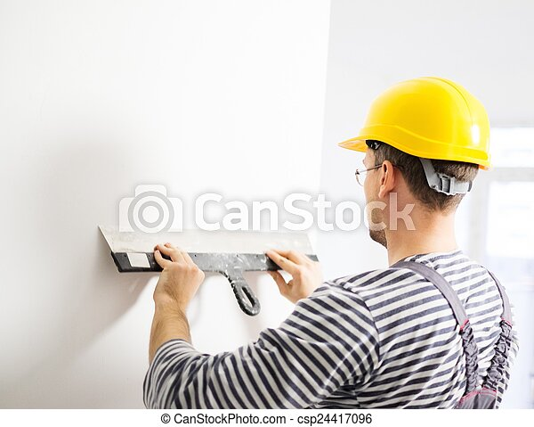 Builder levelling wall with spatula - csp24417096