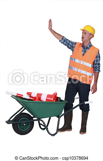 Builder making stop gesture whilst stood with traffic cones - csp10378694