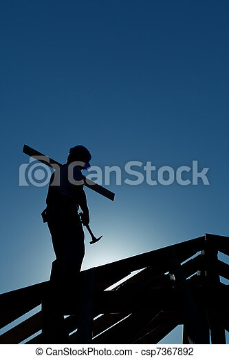 Builder working late on top of building - csp7367892