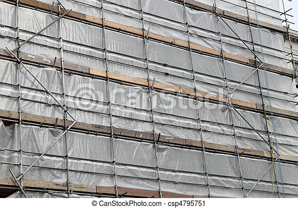 Building covered in scaffolding and tarpaulin for renovation. - csp4795751