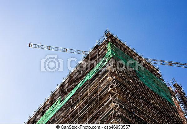 Building crane and building under construction against blue sky - csp46930557