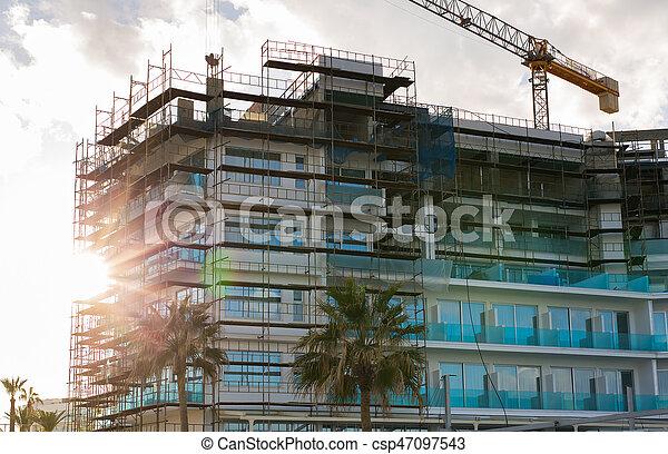 Building crane and building under construction against blue sky - csp47097543