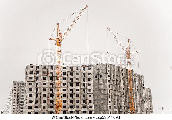 Building crane and building under construction against blue sky - csp53511693
