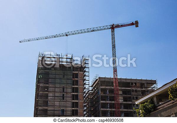 Building crane and building under construction against blue sky - csp46930508
