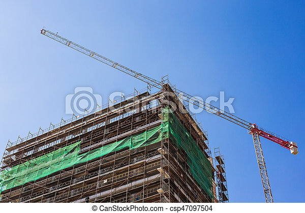 Building crane and building under construction against blue sky - csp47097504