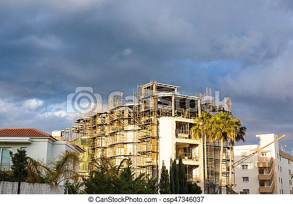 Building crane and building under construction against blue sky - csp47346037