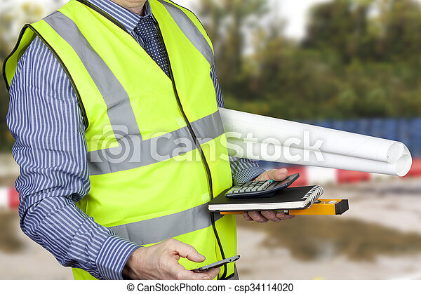 Building surveyor in hi vis carrying site plans and calculator - csp34114020