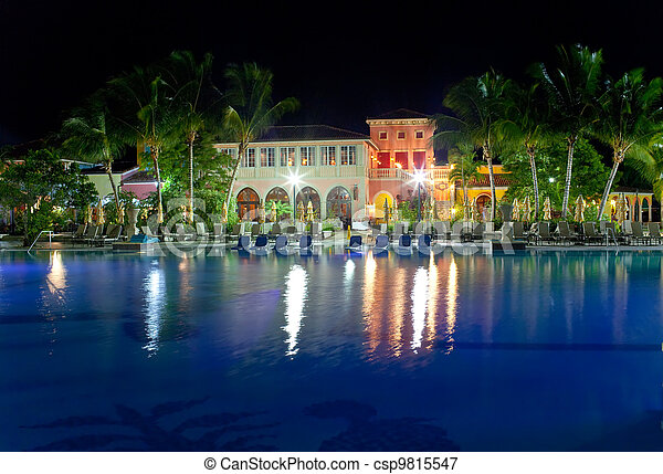 Buildings with night illumination behind pool - csp9815547