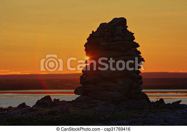 Built from stone Cairn at sunset, at midnight, the polar day - csp31769416