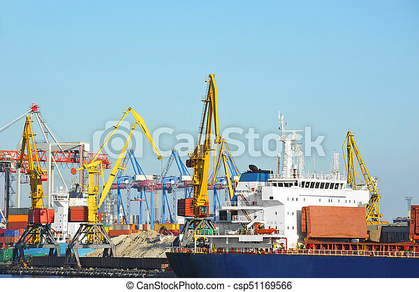 Bulk cargo ship under port crane bridge