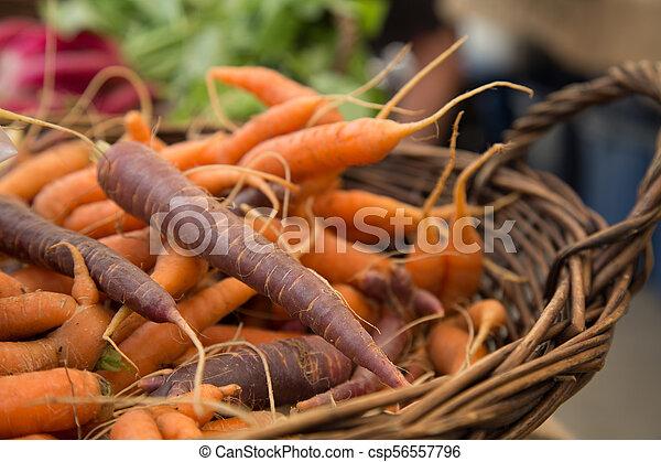 Bunch fresh orange brown carrots basket background - csp56557796