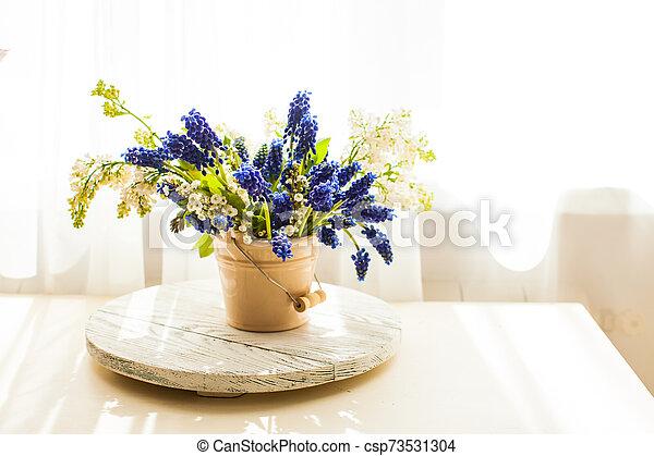 Bunch of grape hyacinths in a ceramic vase - csp73531304