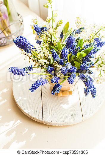 Bunch of grape hyacinths in a ceramic vase - csp73531305