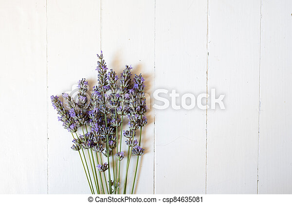 Bunch of lavender flowers lying on a white wooden background - csp84635081