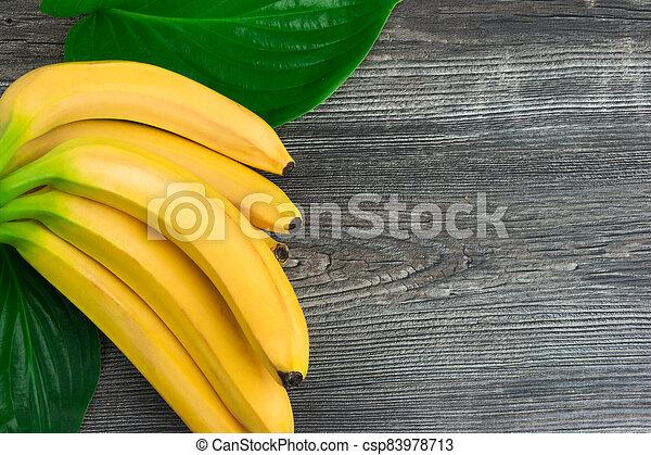 Bunch of raw organic yellow bananas on wooden background - csp83978713