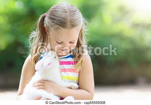Niño con conejo. Conejito de Pascua. Niños y mascotas. - csp55555008