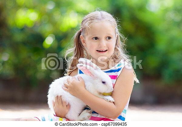 Niño con conejo. Conejito de Pascua. Niños y mascotas. - csp67099435