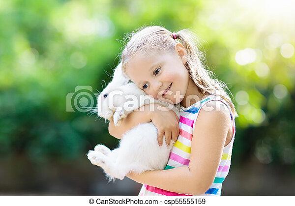 Niño con conejo. Conejito de Pascua. Niños y mascotas. - csp55555159