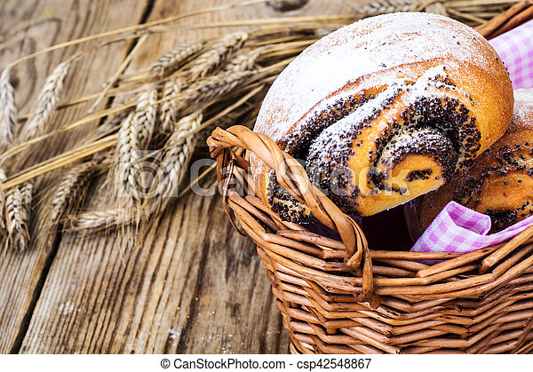 Buns with poppy seeds in a bread basket - csp42548867