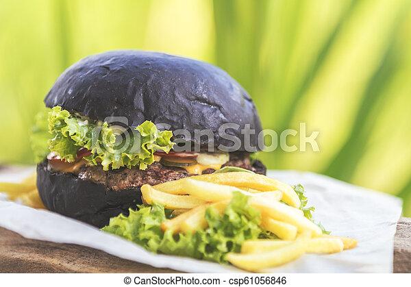 Burger made with black charcoal bun served - csp61056846