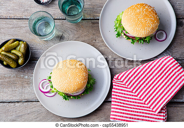 Burger on a plate with pickles. Wooden background. Top view. - csp55438951
