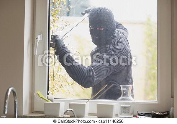 Burglar breaking a kitchen window - csp11146256