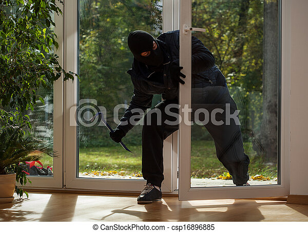 Burglar entering through the balcony window - csp16896885