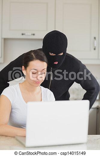 Burglar looking at the laptop behind  woman - csp14015149