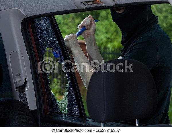 Burglar with crowbar breaking car window - csp23249357