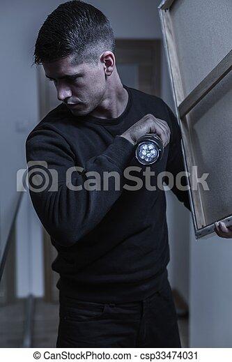 Burglar with flashlight - csp33474031