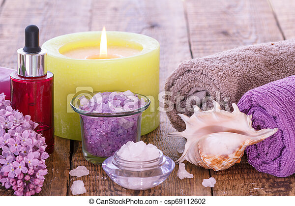 Burning candle, bowls with sea salt, bottle with aromatic oil, lilac flowers and towels on wooden background. - csp69112602