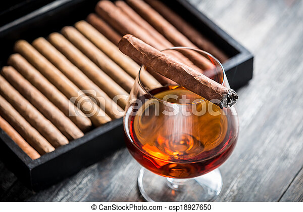 Burning cigar on glass with cognac - csp18927650