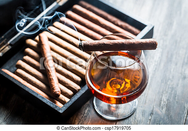 Burning cigar on humidor and cognac in glass - csp17919705