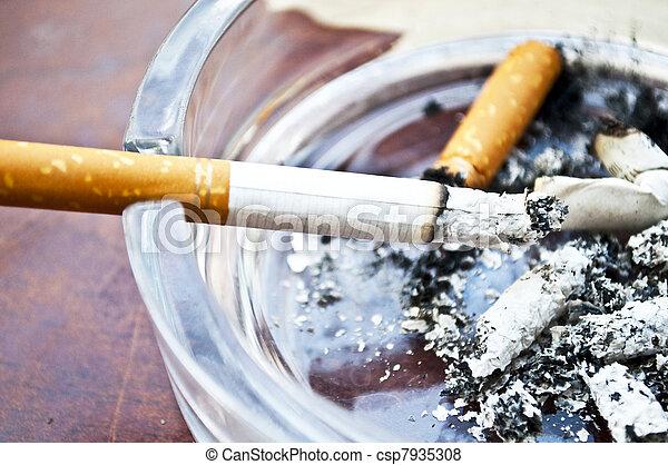 Burning cigarette in ashtray  - csp7935308